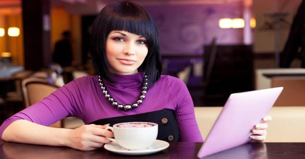 engagin woman looking at ipad and drinking coffee