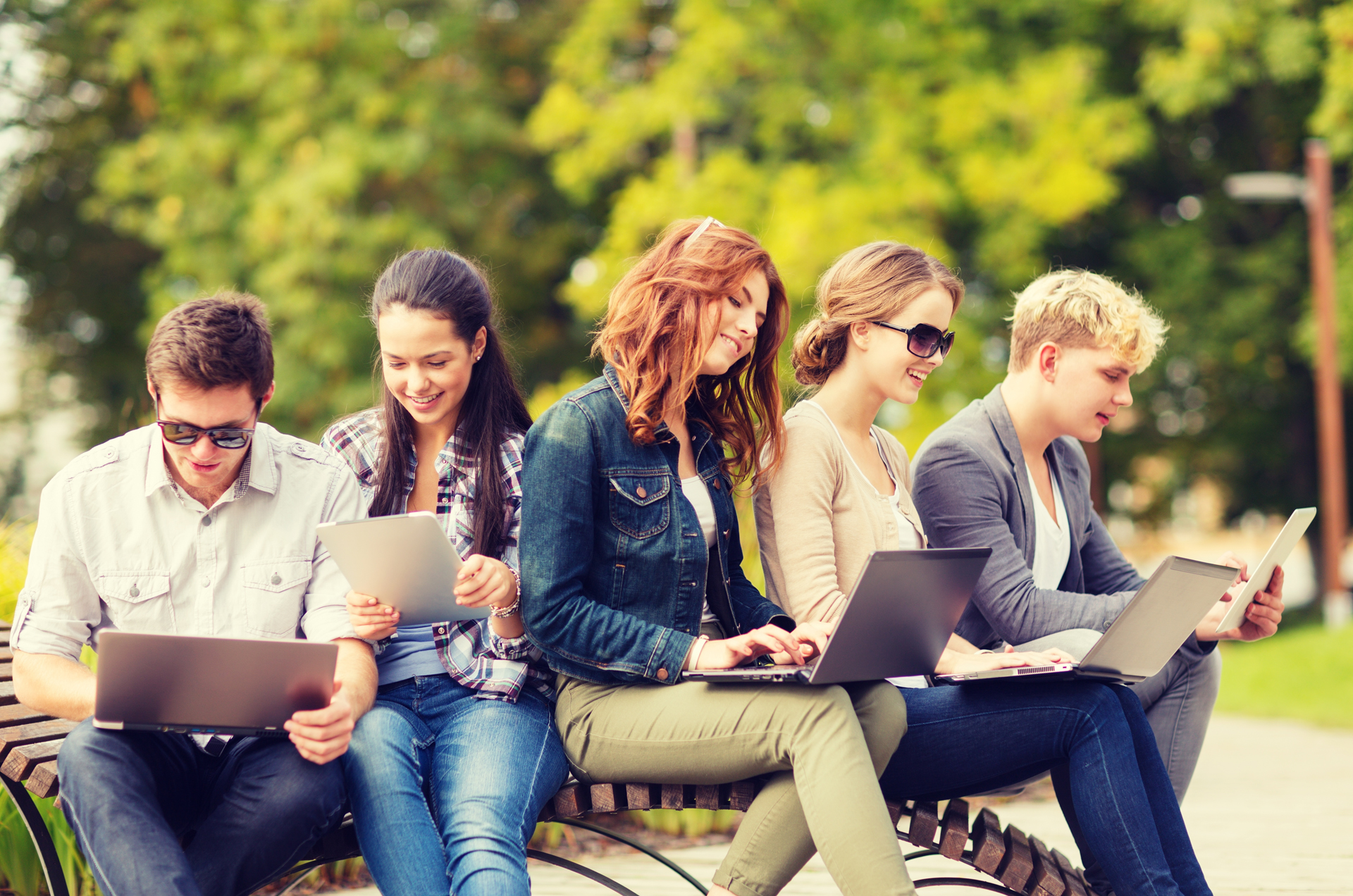 Group of young adults sitting in park all using different mobile devices and laptops