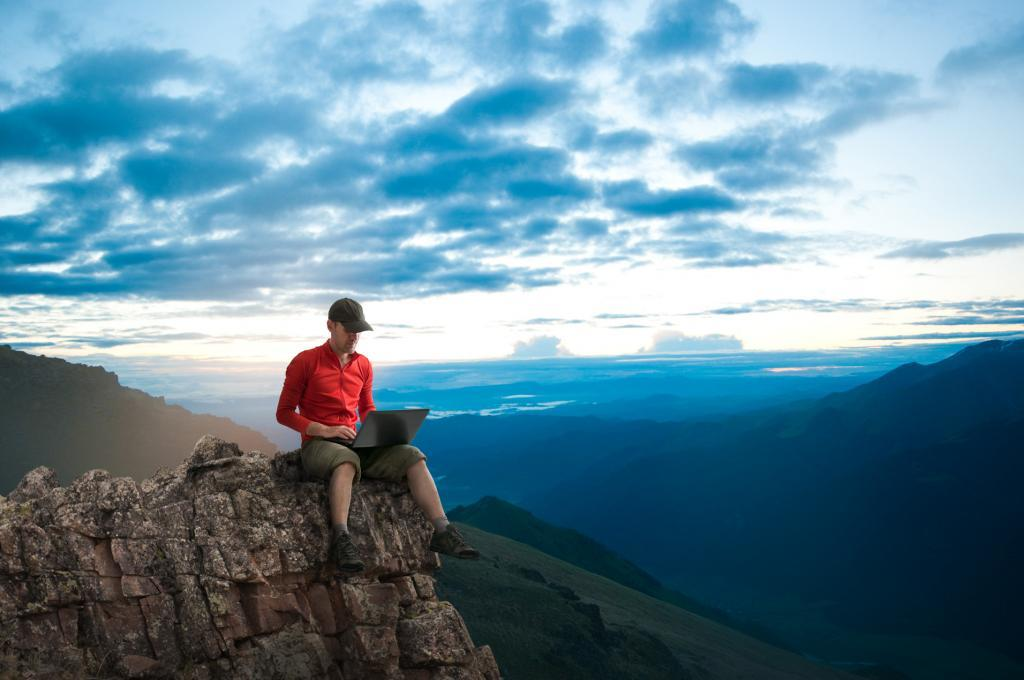 man sitting alone on top of mountain with big blue sky using his laptop